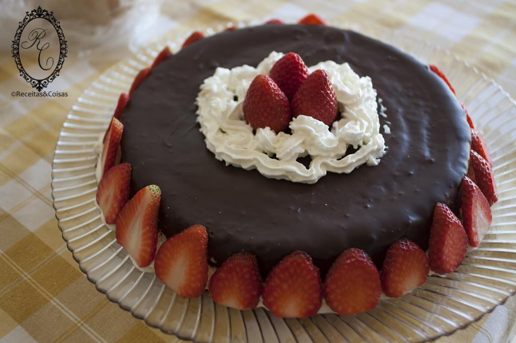 Bolo coberto com chocolate e morangos